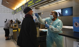 Licensed vocational nurse Caren Williams, left, collects a nasal swab sample from a traveler at a COVID-19 testing site at the Los Angeles International Airport on Monday.
