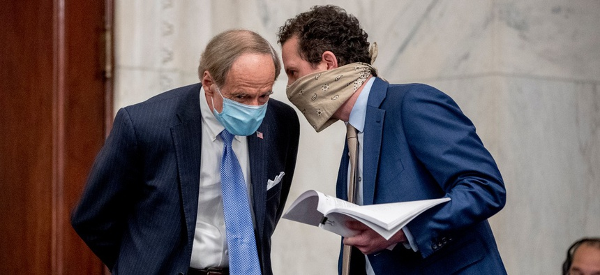 Sen. Tom Carper, D-Del., left, speaks to an aide on Capitol Hill in May. Carper is one of several Democrats keeping an eye on Trump administration efforts to reclassify federal jobs into at-will positions.