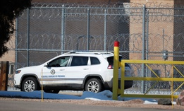 A guard guides a vehicle along the fenceline around the federal correctional institution in Englewood, Colo.