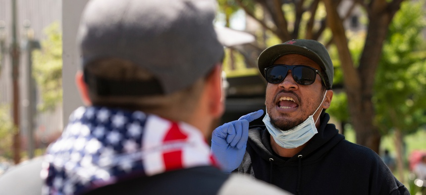 People in front of Los Angeles' City Hall argue during a protest in May.