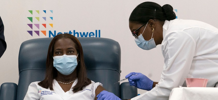 Sandra Lindsay, left, a nurse at Long Island Jewish Medical Center, is inoculated with the Pfizer-BioNTech COVID-19 vaccine by Dr. Michelle Chester, on Monday in the Queens borough of New York.
