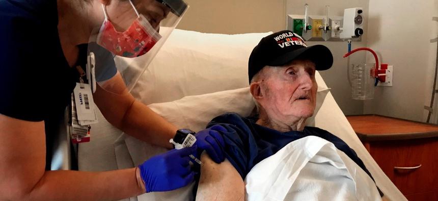 World War II veteran John Mohun, 94, receives the Pfizer-BioNTech COVID-19 vaccine at a Veterans Affairs facility in Phoenix on Tuesday.