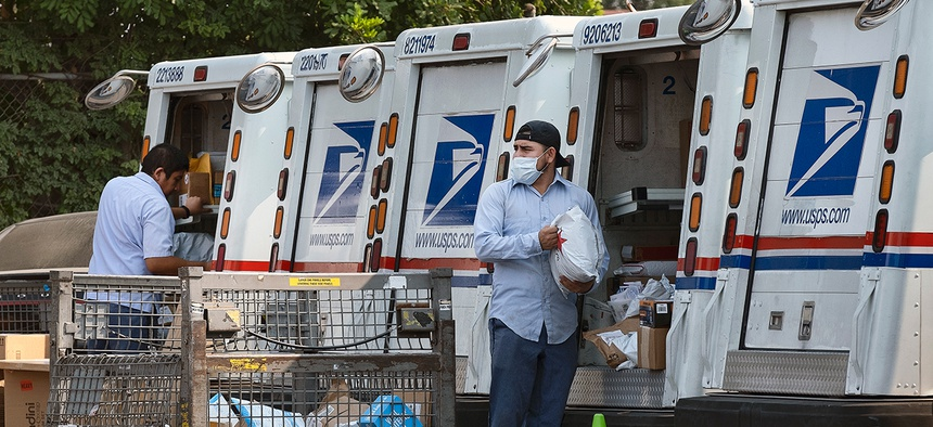 Postal workers load packages in their mail delivery vehicles in Los Angeles in August.