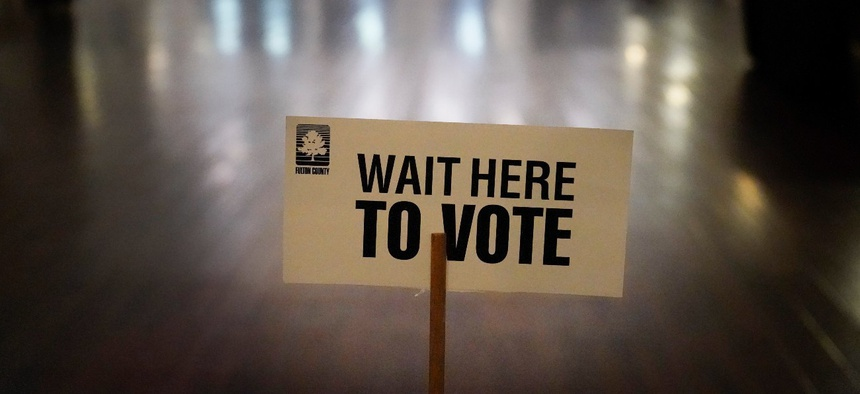 A sign is displayed for voters to guide the way at a precinct during Georgia's Senate runoff elections on Jan. 5, in Atlanta.