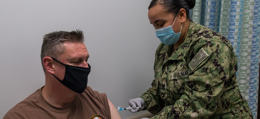 Fleet Master Chief Spike Call, left, Command Master Chief of U.S. 5th Fleet, receives a COVID-19 vaccine from Hospital Corpsman 2nd Class Rose Martinez onboard Naval Support Activity Bahrain, Jan. 4.
