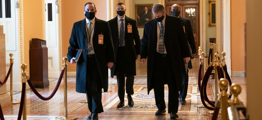 Security officials survey the Capitol on Monday, ahead of the scheduled presidential inauguration.