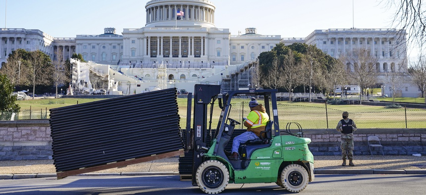 DC National Guard stands outside a mostly quiet Capitol, Thursday morning, Jan. 7, 2021 in Washington, as workers place security fencing in place.