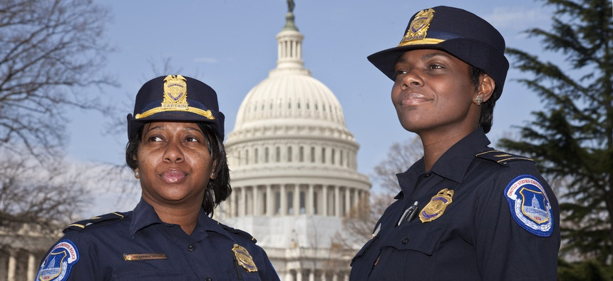 Yogananda Pittman, left, photographed here with fellow Capitol Police officer Monique Moore, right, in 2012. Pittman was appointed to head the Capitol Police force in January 2021, after a riot at the Capitol prompted the resignation of the previous chief