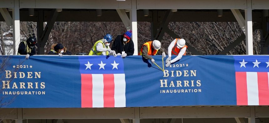 Workers put up bunting on a press riser for the upcoming inauguration of President-Elect Biden and Vice President-Elect Kamala Harris, on Pennsylvania Avenue in front of the White House.