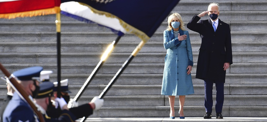 President Joe Biden salutes as his wife Jill puts her hand over her heart as they review the troops from the steps of the U.S. Capitol during the inauguration.