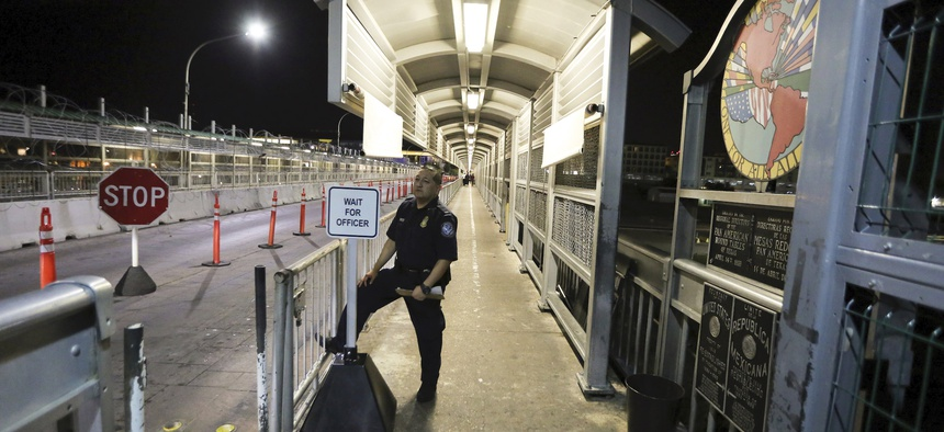 A Customs and Border Protection officer waits for migrants who are applying for asylum in the United States to arrive at International Bridge 1 where they will cross from Nuevo Laredo, Mexico, to Laredo, Texas in 2019.