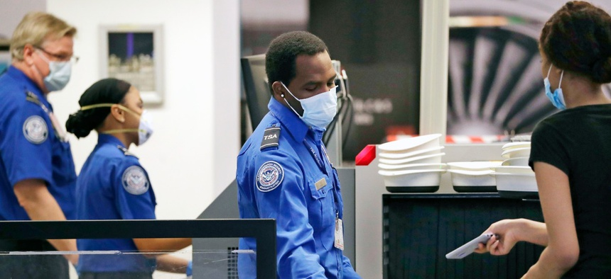 TSA officers screen passengers at Seattle-Tacoma International Airport.