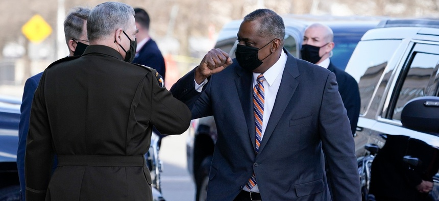 Defense Secretary Lloyd Austin, right, greets Chairman of the Joint Chiefs of Staff Mark Milley as he arrives at the Pentagon on Friday.