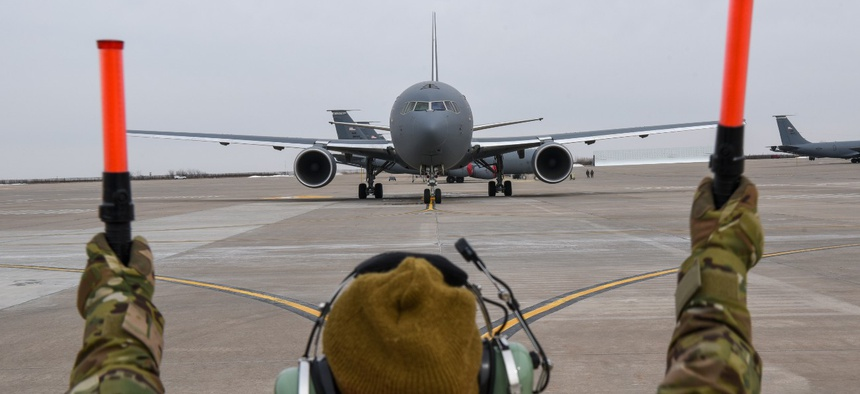 A crew chief marshals a KC-46A Pegasus on the flightline at McConnell Air Force Base in Kansas.
