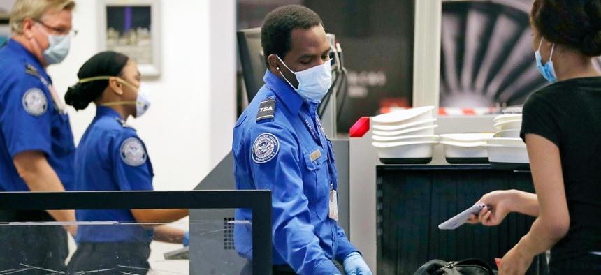 TSA officers wear protective masks at a security screening area at Seattle-Tacoma International Airport in May 2020.