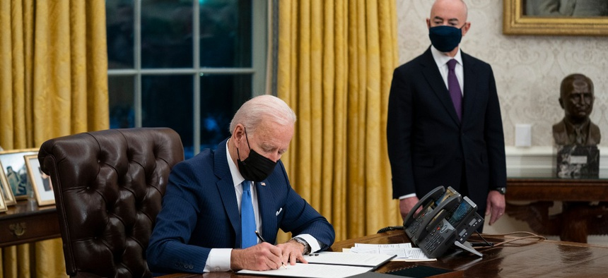 President Joe Biden talks with newly sworn in Homeland Security Secretary Alejandro Mayorkas before signing executive orders on immigration on Tuesday.