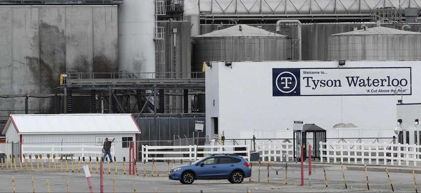 In this Friday, May 1, 2020, photo, a worker leaves the Tyson Foods plant in Waterloo, Iowa.