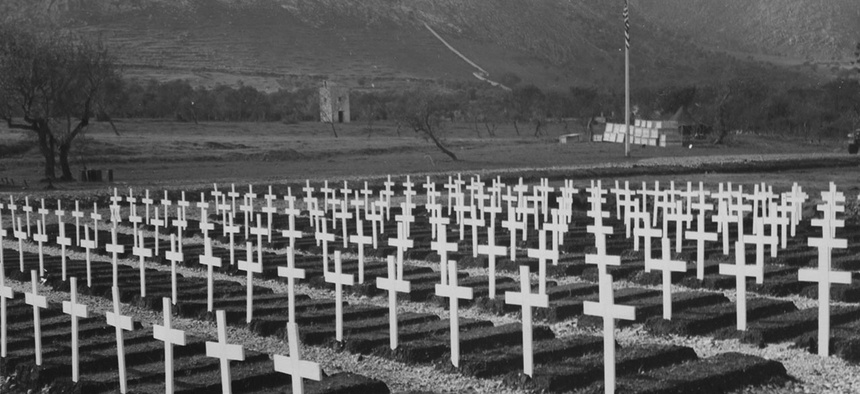 Graves of American war dead mark the mountain valley floor an officers and men of all arms of the service form for Armistice day ceremonies at the military cemetery in Palermo, Sicily