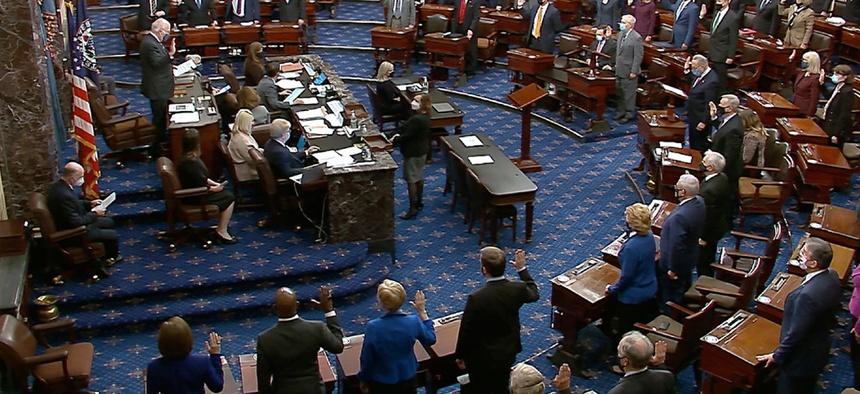 In this Jan. 26 image from video, Sen. Patrick Leahy, D-Vt., the president pro tempore of the Senate, who is presiding over the impeachment trial of former President Trump, swears in members of the Senate for the trial.