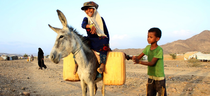 A girl rides a donkey carrying jerry cans filled with water from a cistern at a make-shift camp for displaced Yemenis in a severe shortage of water, in the northern Hajjah province on March 24, 2020.