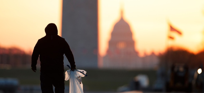 A National Park Service worker picks up trash along the drained Lincoln Memorial Reflecting Pool as the Washington Monument and the U.S. Capitol are seen in the distance in Washington, at sunrise.