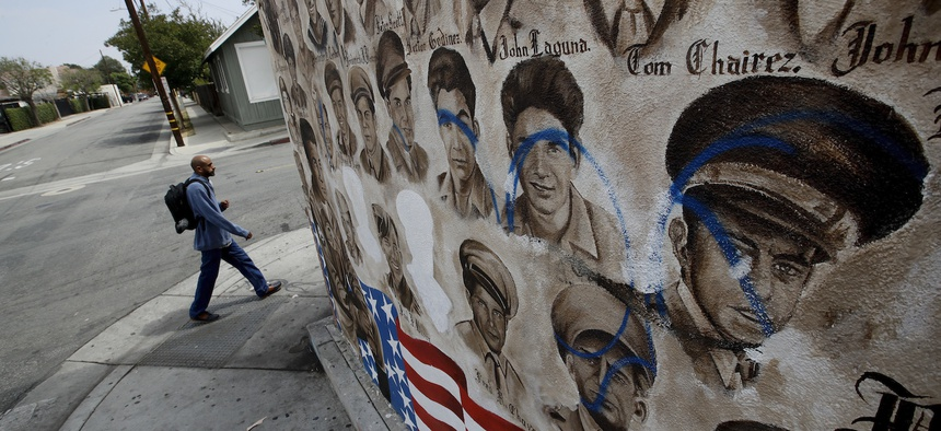 A person walks by a mural that features nearly 200 portraits of Mexican-American men and women who have served in World War II, the Korean War and the Vietnam War Tuesday, May 29, 2018, in Santa Ana, Calif.