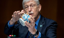 Dr. Francis Collins, director of the National Institutes of Health, holds up a model of COVID-19, known as coronavirus, during a Senate hearing in July.