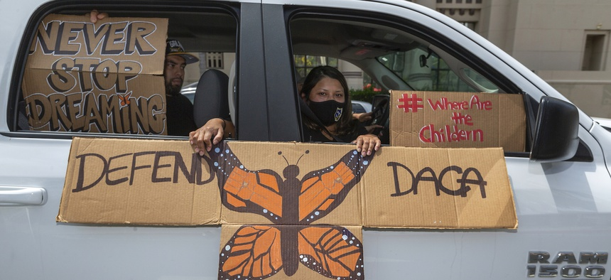 People hold signs during a vehicle caravan rally to support the Deferred Action for Childhood Arrivals Program (DACA), around MacArthur Park in Los Angeles in June 2020.