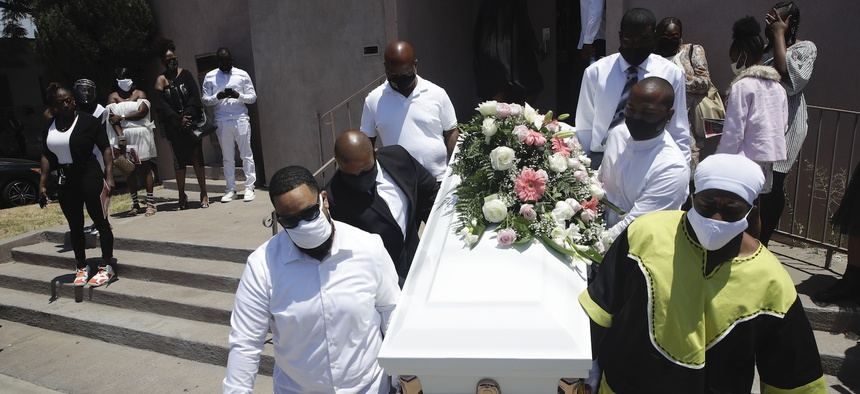 Pall bearers carry a casket with the body of Lydia Nunez, who died from COVID-19, after a funeral service at the Metropolitan Baptist Church in Los Angeles in Jully