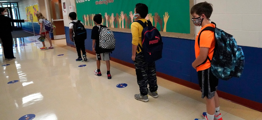 Students keep a social distance as they walk to their classroom at Oak Terrace Elementary School in Highwood, Ill. The Education Department is receiving $170 billion from the American Rescue Plan.