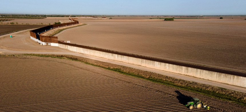 Border wall construction is seen near farmland as a tractor plows a field on March 19, 2021, in Progreso, Texas.