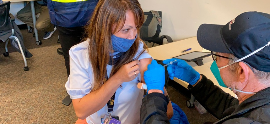 Grace John, who works at a school in San Lorenzo, gets a COVID-19 shot at a mobile vaccination clinic run by the Federal Emergency Management Agency and the state in Hayward, Calif., on Friday, Feb. 19, 2021.