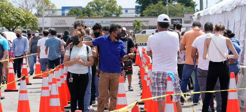 People wait in line to receive a COVID-19 vaccine at a FEMA vaccination center at Miami Dade College on Monday. Any adult in Florida is now eligible to receive the coronavirus vaccine.