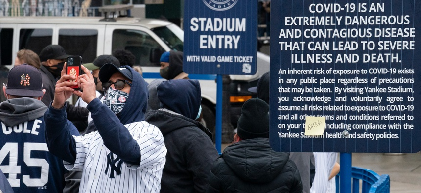 Spectators wait in a security line outside Yankee Stadium before an opening day baseball game against the Toronto Blue Jays on April 1. Schools, businesses and sports and entertainment venues are considering rapid COVID-19 tests as a requirement for entry