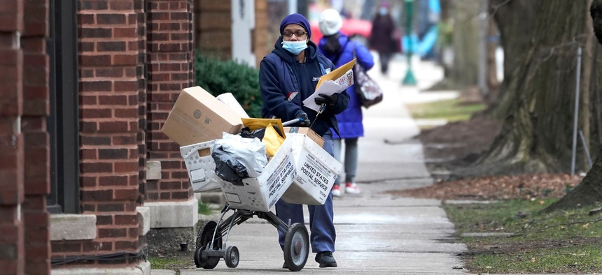A U.S. postal worker delivers packages, boxes and letters on Dec. 22, 2020, along her route in the Hyde Park neighborhood of Chicago.