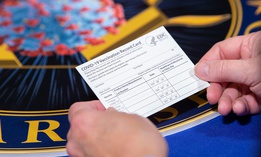A Department of Health and Human Services employee holds a COVID-19 vaccine record card Nov. 13, 2020, in Washington D.C.